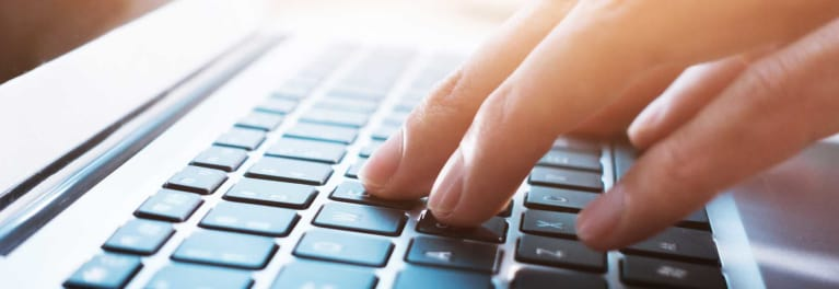 A person using keyboard shortcuts on a laptop.
