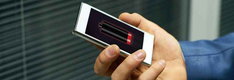 A person holding a smartphone with low battery life.