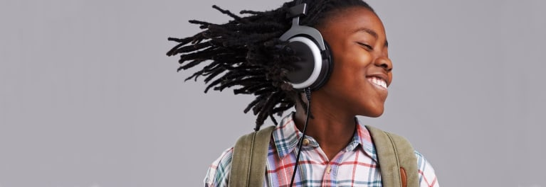 Photo of a child wearing a set of headphones, for an article on the best cheap headphones for back-to-school shoppers.