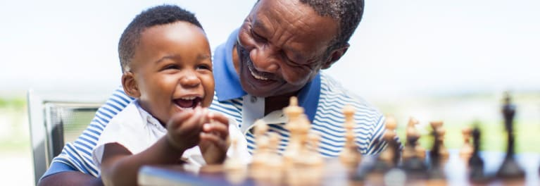 A smiling grandfather and his toddler grandson sitting in front of a chessboard.