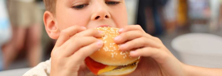 Boy eats a hamburger from one of many chains' kids menus.