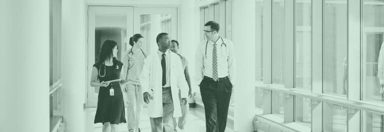 Healthcare professionals walking in a hallway.