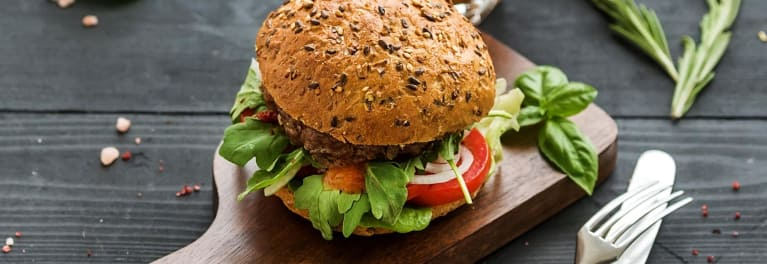 A healthy burger with lettuce and tomato on a seeded bun.