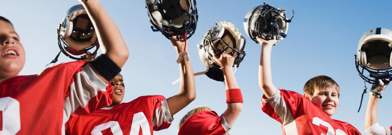 A group of junior football players with their helmets, which help prevent concussions in children.