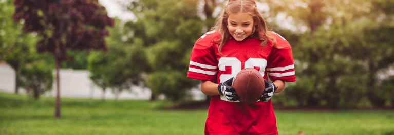 A young girl in a football uniform.