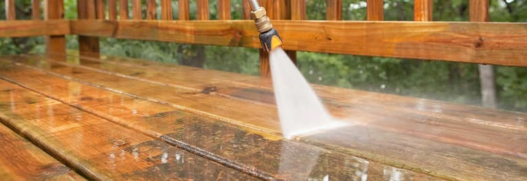 Using a pressure washer to clean a wood deck.