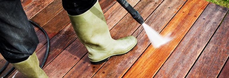 A person in rubber boots pressure washing a deck