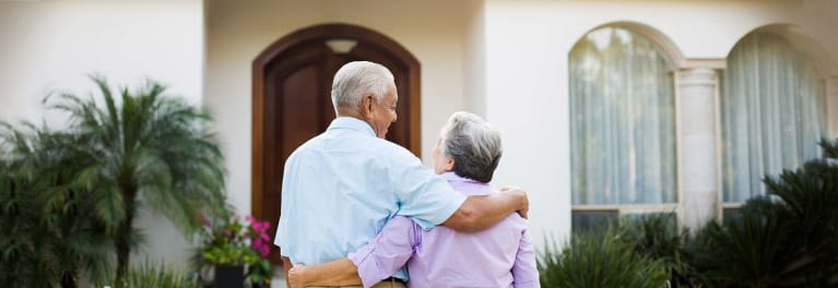 An elderly couple hugging in front of their home