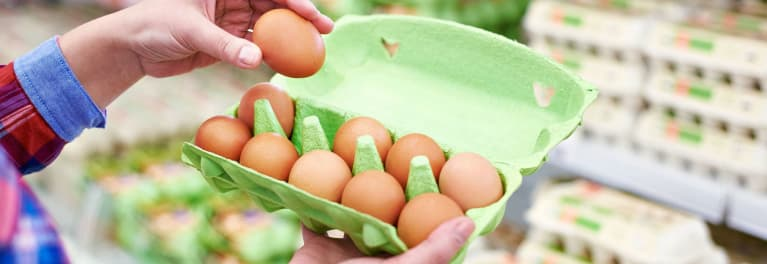 A shopper checks an egg carton for cracked eggs, one of many important food-shopping safety tips that experts recommend.