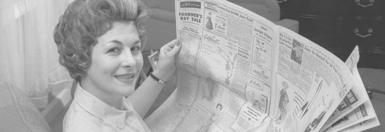 Selling It - A vintage photograph of a housewife reading a newspaper's advertisement section.