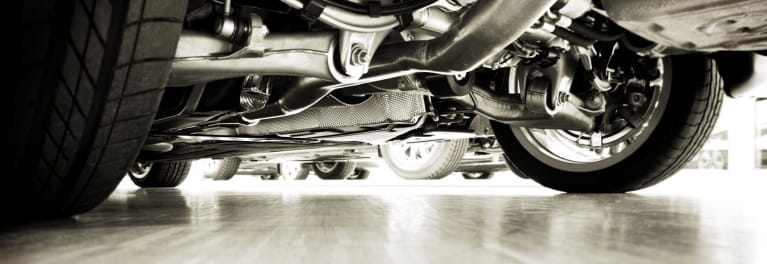 The undercarriage of a car to demonstrate the constant need for car repairs and the ongoing cost of car ownership
