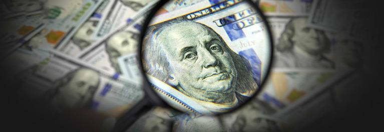 A hundred dollar bill under a magnifying glass.