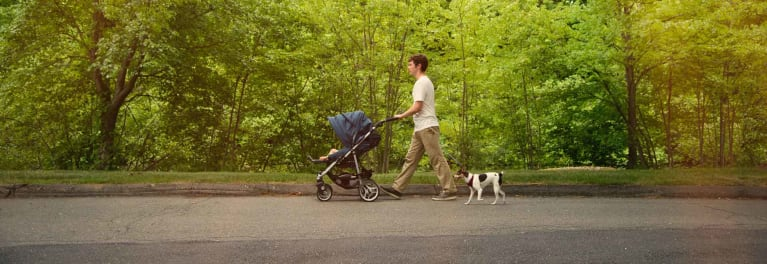Image of a parent pushing a stroller in a park. The best strollers from Consumer Reports' tests