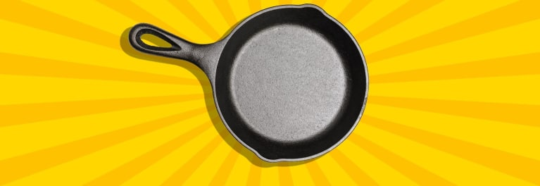 A cast-iron skillet on a yellow background.