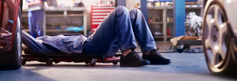 A mechanic looking under a car to illustrate a car recall
