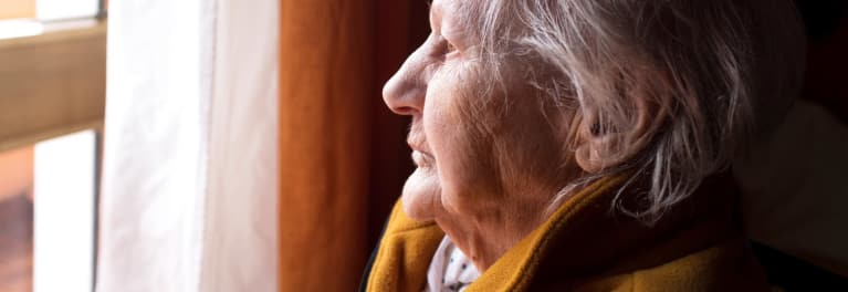 An elderly woman looking through her window.