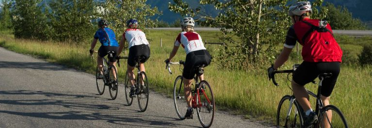 Four people riding bikes on country road. Proper riding technique can help prevent a bike accident.
