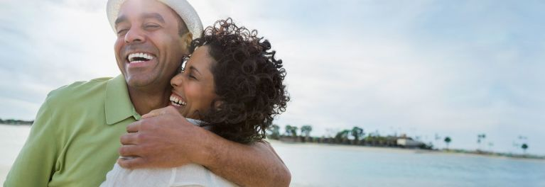 A photo of a happy man and woman with an island in the background. Finding the perfect holiday gifts for travelers who go to such exotic places can be made easier with Consumer Reports' helpful list of gift ideas.