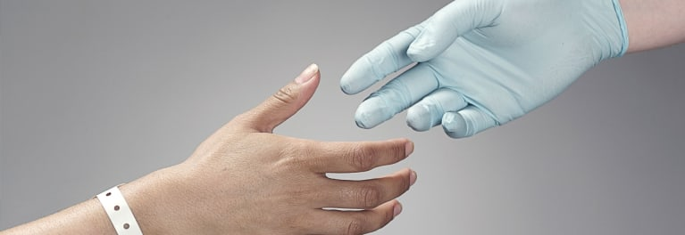 An image of a doctor's hand reaching out to a patient.