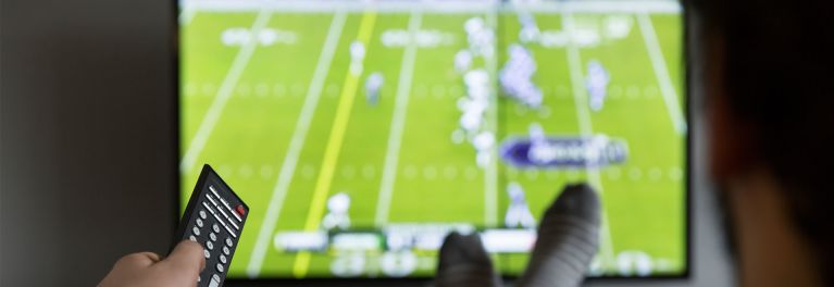 Photo of a TV viewer watching football for an article on how many cable customers would dump ESPN to save $8 a month