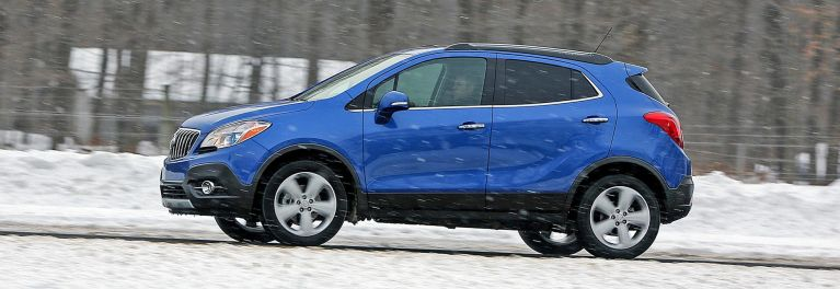 A blue car in snowy weather.