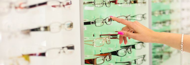 Woman with finger on pair of eyeglass lenses.