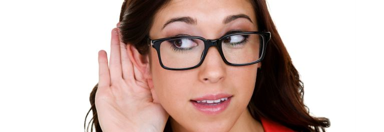 Young woman cupping her ear to hear better.