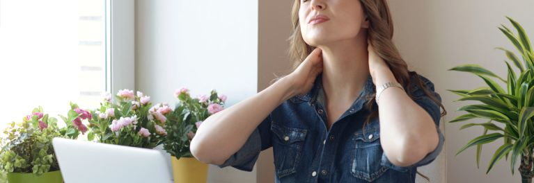 Woman putting arms up to neck looking for relief from neck pain.