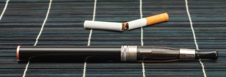 This is an image of an e-cigarette, or vape pen, next to a broken tobacco cigarette.