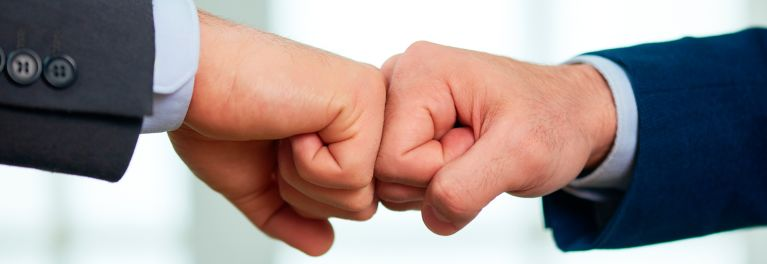 Close up of two men's hands doing the fist bump. Replacing a handshake with a fist bump can help you stay healthy this winter.