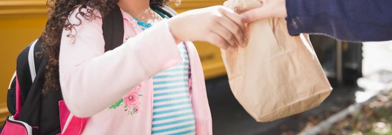 Parent handing child lunch in a brown bag. Brown bag lunches are important for kids with food allergies.