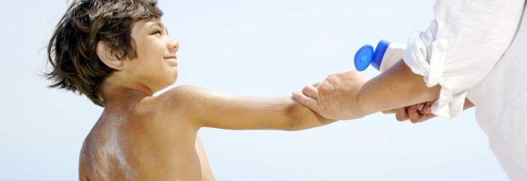 Parent putting sunscreen on a child. Natural sunscreen may underperform according to Consumer Reports' tests.