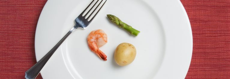 A portion control meal with shrimp, asparagus, and a potato.