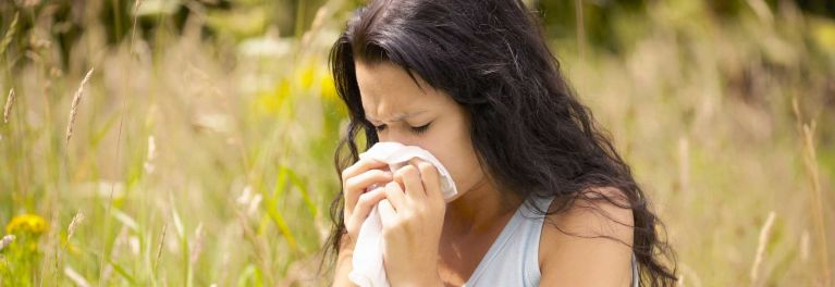Photo of a woman blowing her nose. Allergy treatments like immunotherapy can prevent symptoms.