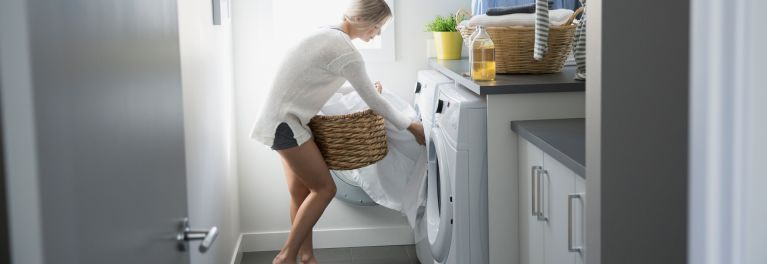 This is a photo of a woman taking clothes out of a dryer. A hot dryer can help reduce dust mites on clothing. Dust mites can cause allergy symptoms.
