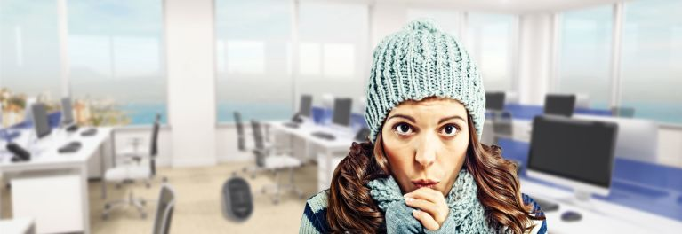 Woman shivering in overly cold office.