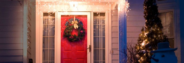 Getting ready for the holidays: A Christmas wreath on a red door of a house.