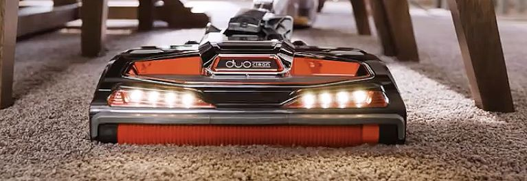 A vacuum on carpeting under furniture.