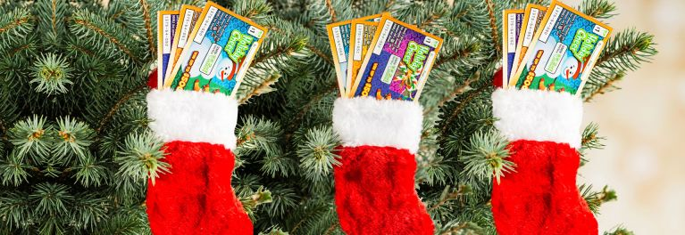 "An image of three red Christmas stockings stuffed with various ""scratch-and-win"" lottery tickets."