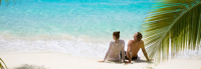 A couple relaxes on a tropical beach, where mosquitos infected with the Zika virus are a threat..