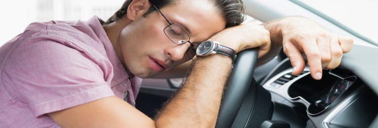 Man asleep at the wheel of a car