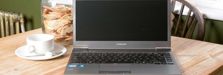 A Toshiba laptop on a table beside a coffee cup.